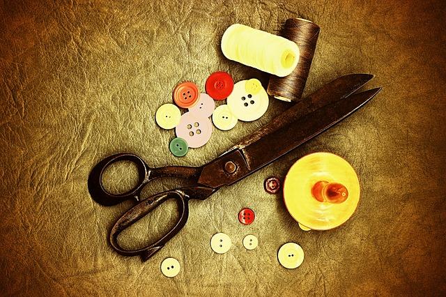 knoflíky, nitě a nůžky na ponku